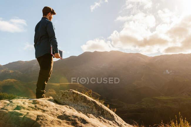 Спокійний самець - дослідник з планшетом, що стоїть на скелі і має захопливий вид на гори в сонячний день. — стокове фото