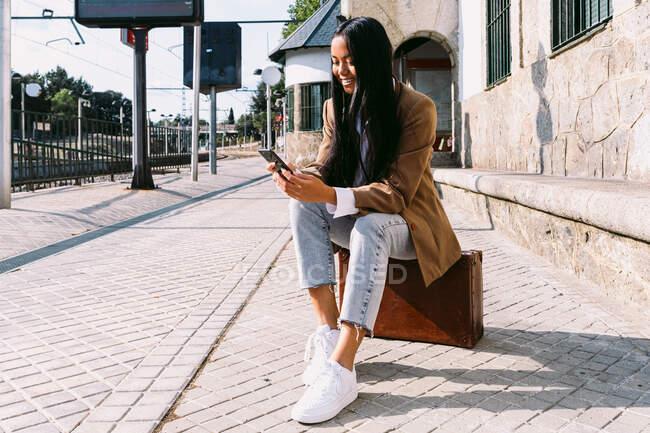Alegre asiático viajando hembra sentado en vintage maleta en la plataforma en la estación de tren y la navegación del teléfono móvil, mientras que la espera de tren - foto de stock