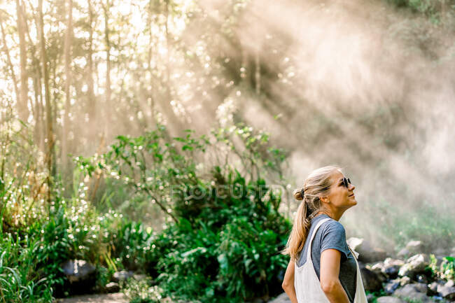 Side view of young woman sitting on stone near calm lake and magnificent waterfall on sunny day — Stock Photo