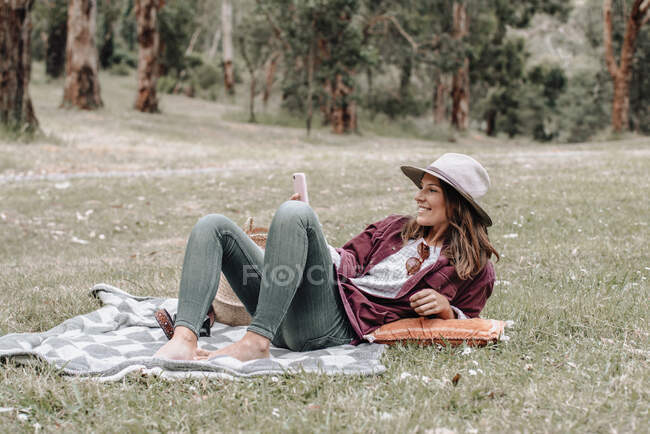 Cheerful female in hat sitting on blanket on meadow in forest and browsing mobile phone while enjoying picnic in Australia — Stock Photo