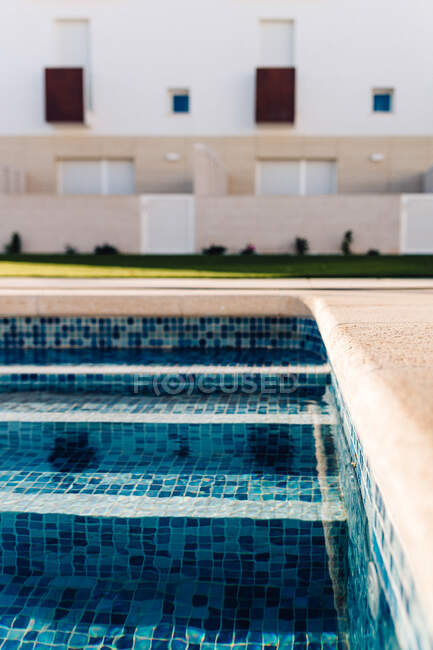 Contemporary house exteriors against swimming pool with rippled water and lawn under blue sky in city — Stock Photo