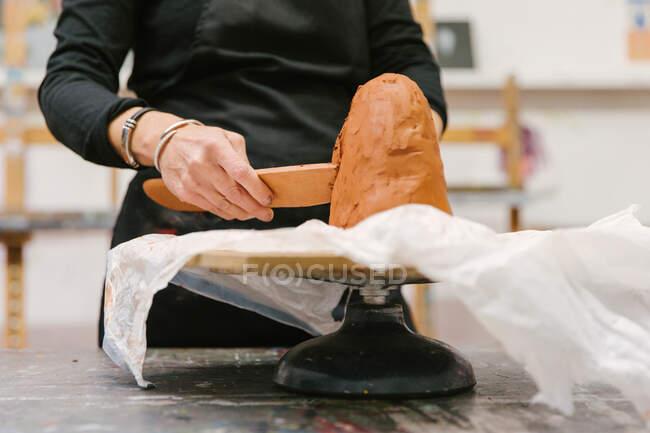Нерозпізнавана жінка - керамік використовує глину і створює керамічний глиняний виріб у художній студії. — стокове фото