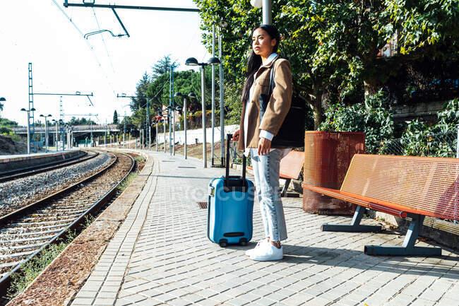 Обабічний вид азіатської жінки - мандрівника з валізою на платформі залізничної станції в очікуванні поїзда. — стокове фото