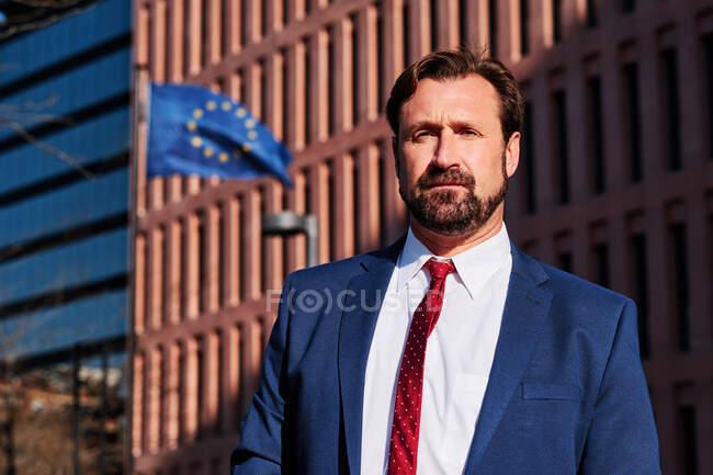 Неголений чоловік-виконавчий у костюмі краватки, що дивиться на багатоповерховий будинок і прапор Європи в місті. — стокове фото