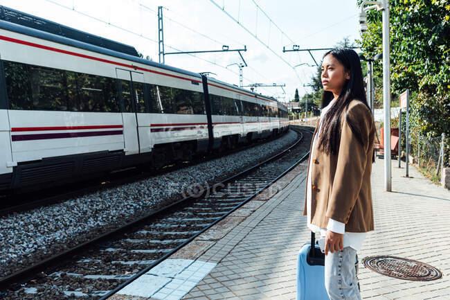 З боку погляд азіатської жінки-мандрівника з валізою на платформі залізничної станції і погляд на поїзд. — стокове фото