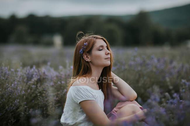 На вигляд лагідна самиця з квітами в волоссі сидить на квітучому лавандовому полі і насолоджується природою закритими очима. — стокове фото