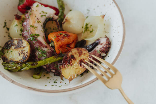 High angle of tasty grilled potatoes near peppers and onions with cooked octopus in bowl with chopped parsley — Stock Photo