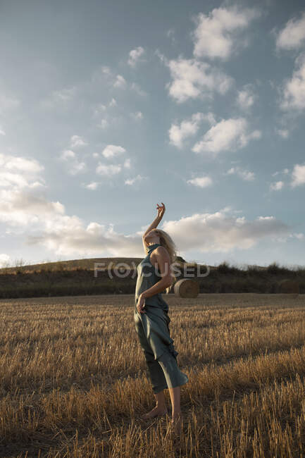 Peaceful female in elegant dress standing on dry field in rural area and closed eyes — Stock Photo