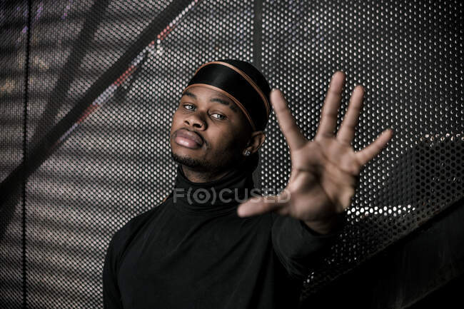 Black male in trendy hat showing stop sign while standing in underground parking and looking at camera — Stock Photo