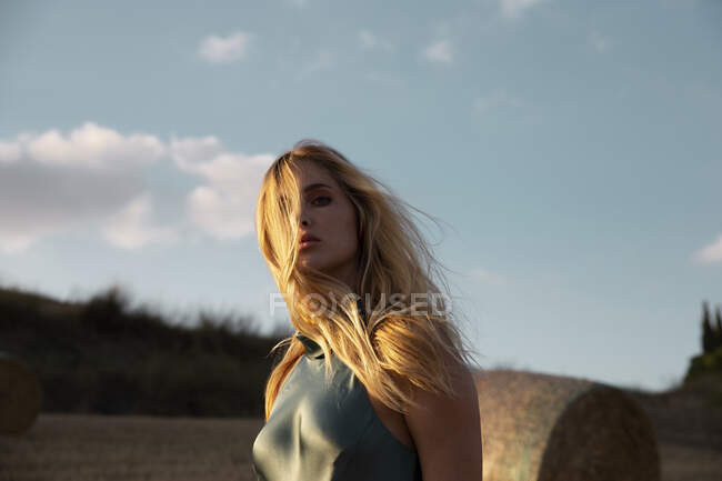 Peaceful female in elegant dress standing on dry field in rural area and looking at camera — Stock Photo
