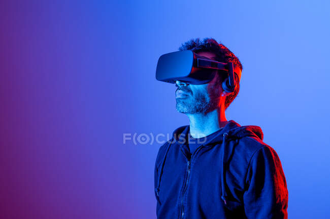 Unrecognizable bearded male in headset exploring virtual reality in neon light — Stock Photo