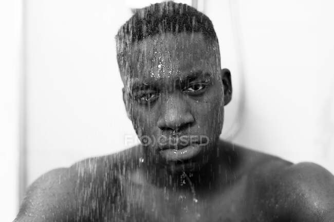 Black and white of emotionless young black guy taking shower in light bathroom and looking at camera and water on face — Stock Photo