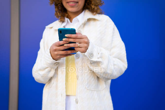 Cropped unrecognizable delighted African American female using smartphone while standing on blue background — Stock Photo