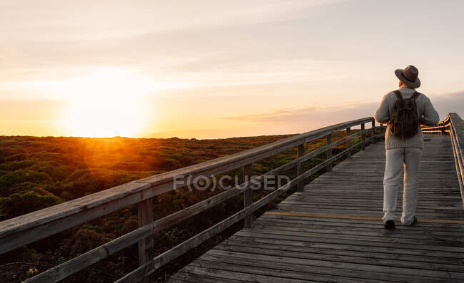 Man with backpack and hat walking on a walkway looking the horizon — Stock Photo