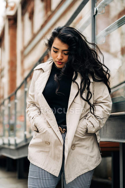 Low angle of plus size female wearing trendy coat standing with hands in pockets against city street and looking down — Stock Photo
