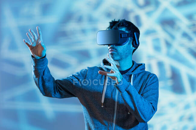 Unrecognizable bearded male in hoodie and modern headset exploring virtual reality in neon light — Stock Photo