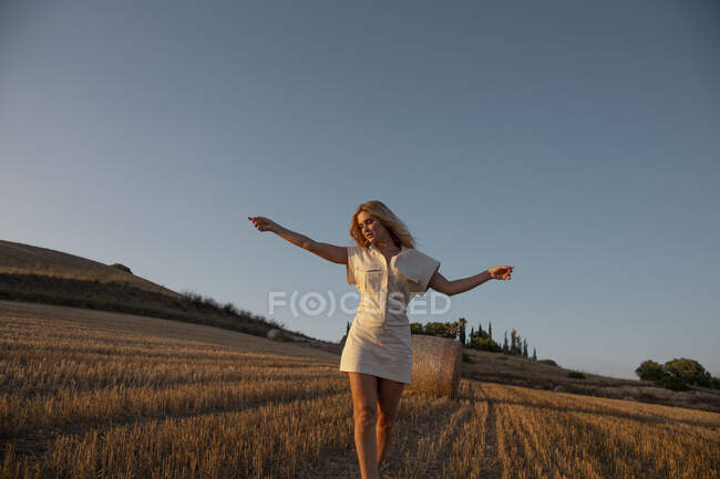 Peaceful female in elegant dress standing on dry field in rural area and looking down — Stock Photo