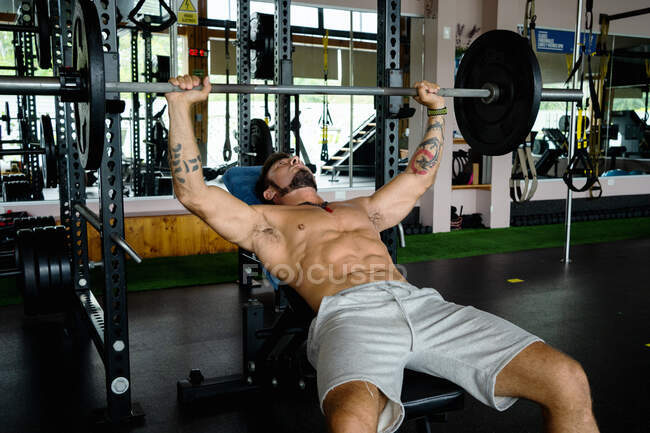 Powerful male athlete doing bench press exercise with heavy barbell while training in contemporary gym — Stock Photo