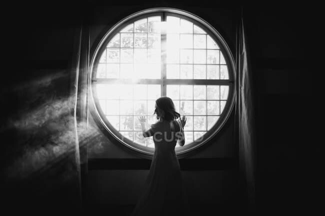 На задньому плані непомітна ніжна жінка дивиться через плече дотик огорожі круглої форми вікна в будинку під сонячним світлом — стокове фото
