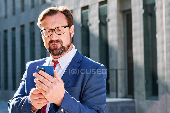 Serious male executive manager in suit standing in downtown and surfing Internet on mobile phone — Stock Photo