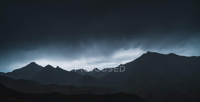 Landscape of Aran valley with majestic green hills and dark gray gloomy sky above — Stock Photo
