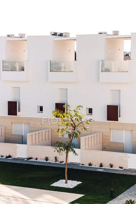 Exteriores de la casa contemporánea contra la piscina con agua ondulada y césped bajo el cielo azul en la ciudad - foto de stock