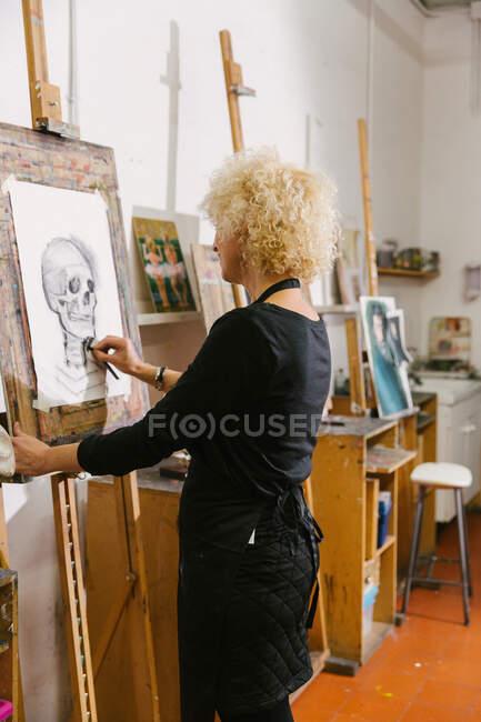 Vista lateral de artista feminina talentosa em pé no cavalete e desenho em papel com lápis no estúdio de arte — Fotografia de Stock