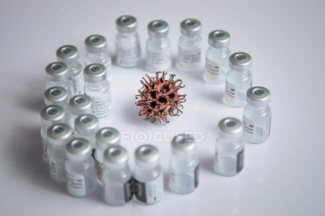 Simulação microscópica do padrão do vírus COVID-19 no fundo cercado por frascos de vacina — Fotografia de Stock