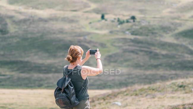 Під час літньої подорожі сонячним світлом на мобільному телефоні зображений анонімний жіночий рюкзак, який фотографує пагорби. — стокове фото