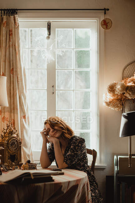 Young mindful female with closed eyes leaning on hands at table with books against window in house on sunny day — Stock Photo