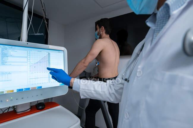 Médico de cultivo analizando datos sobre monitor digital durante la prueba de esfuerzo cardíaco del paciente masculino que camina en la cinta de correr - foto de stock