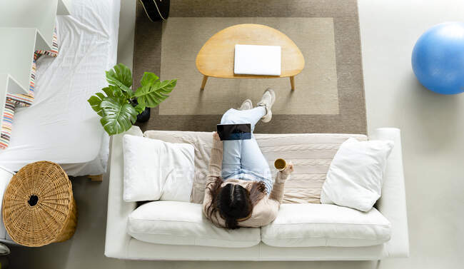 From above young female with tablet and cup of hot beverage resting with crossed legs on couch in living room — Stock Photo