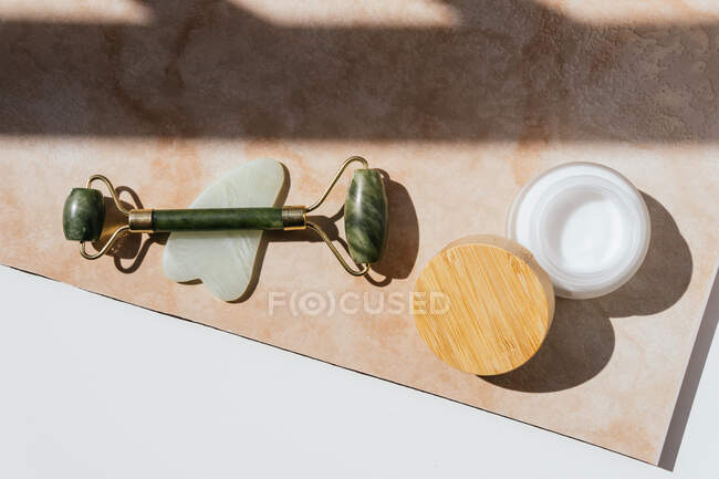 Top view of jade roller, guasha scraper and natural facial cream arranged on marble table for concept of face massage — Stock Photo
