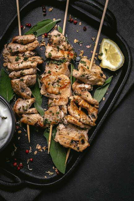 De arriba de la carne apetitosa recién cocida a las brochetas servidas en la bandeja a la mesa negra con el plato de la salsa - foto de stock