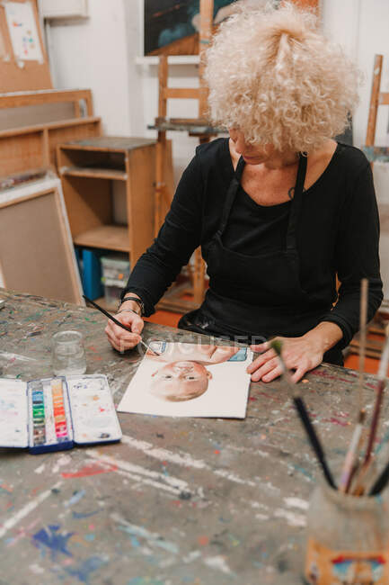 High angle of female artist in apron painting with watercolors on paper while sitting at table in creative workshop — Stock Photo