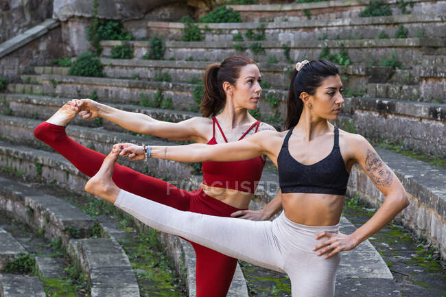 Гибкие женщины в спортивной одежде практикуют йогу в Utthita Hasta Padangusthasana, балансируя на каменных ступеньках и отводя взгляд — стоковое фото