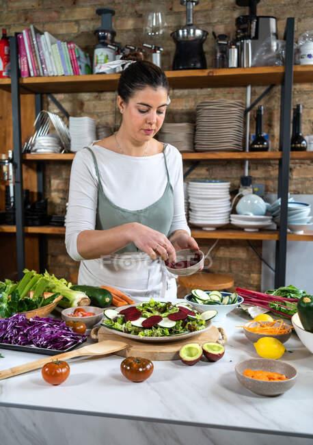 Hembra con remolacha fresca en un tazón preparando ensalada vegetariana almuerzo en casa cocina - foto de stock