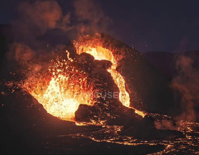 Primer plano Volcán Fagradalsfjall en erupción en Islandia entre nubes de humo - foto de stock
