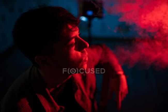 Pensativo macho fumar narguile mientras se relaja en oscuro edificio de mala calidad iluminado por luces de neón rojo y azul - foto de stock