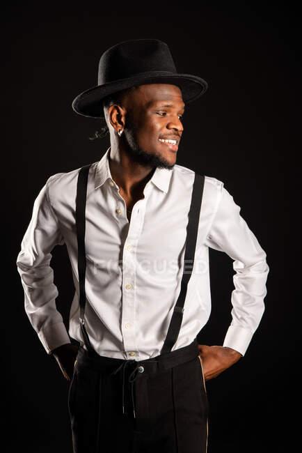 Jovem masculino étnico masculino modelo no chapéu e calças de pé enquanto olhando para longe no fundo preto com fumaça — Fotografia de Stock