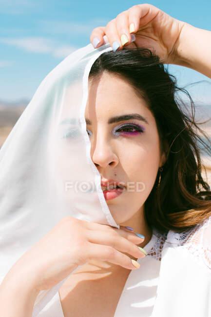 Jovem morena cobrindo o olho com véu enquanto olha para a câmera no dia do casamento — Fotografia de Stock