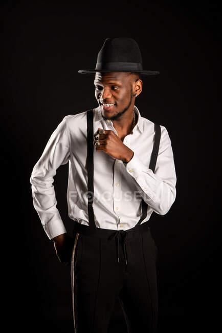 Молоді чоловіки, етнічні чоловічі моделі в капелюсі і штанях стоять, дивлячись на чорне тло з димом. — стокове фото