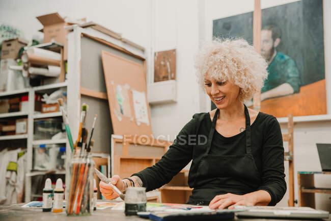 Artista feminina focada sentada à mesa e pintando com aquarelas em papel enquanto trabalhava em oficina criativa — Fotografia de Stock