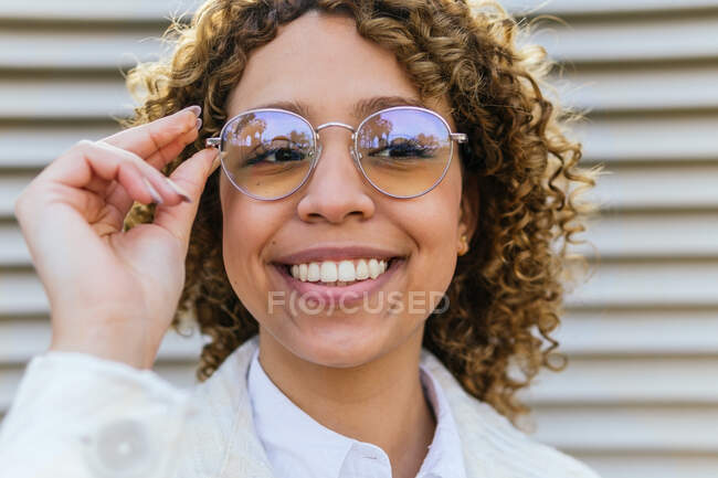 Delighted young African American female with curly hair touching trendy sunglasses and looking away in city — Stock Photo