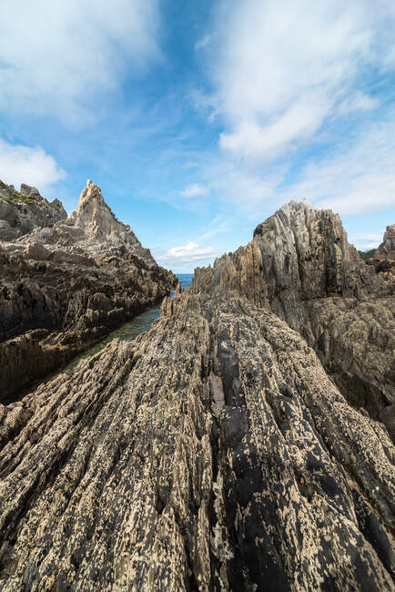 Scenic view of rocky formations on Gueirua beach near calm sea under blue sky in Asturias — Stock Photo