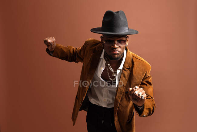 Young African American male in trendy apparel and hat dancing looking at camera — Stock Photo