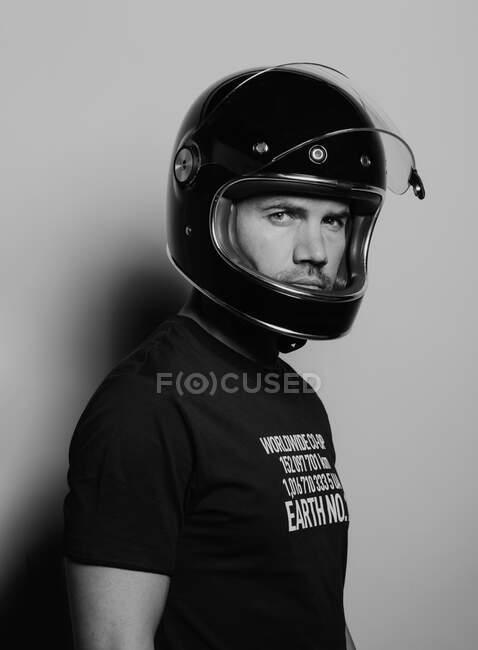 Бічний вид упевненого жорстокого дорослого чоловіка в чорному шоломі мотоцикла дивиться на камеру, стоячи навпроти студійного фону — стокове фото