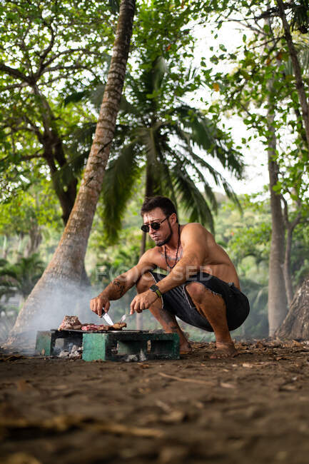 Homem adulto sem camisa com óculos de sol e colar preparando carne saborosa na grelha no dia ensolarado na natureza — Fotografia de Stock