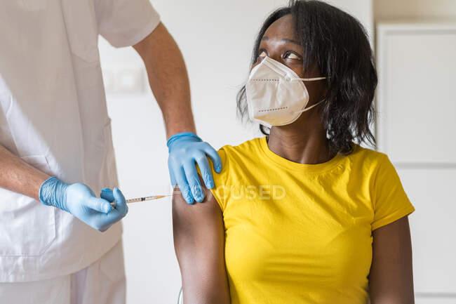 Cultivado especialista médico masculino irreconhecível em luvas de látex protetoras vacinando paciente afro-americano na clínica durante o surto de coronavírus — Fotografia de Stock