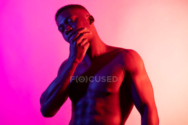 Serious young African American male athlete with naked torso looking at camera and touching face on pink background in neon studio — Stock Photo
